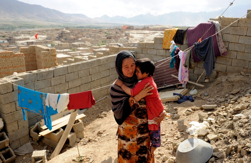An Afghan returnee Sadiqa, 30, holds her daughter in her shetter yard in Kabul, Afghanistan, June, 11, 2012. Sadiqa and her family returned to Afghanistan 7 years ago after living for 5 years in Pakistan and are building their home by the support of Norwegian Refugee Council shelter programs in Afghanistan.  Norwegian Refugee Council shelter program in Afghanistan targets internally displaced persons, returning Afghan refugees and host communities by providing shelter interventions include short-term emergency shelter and longer-term permanent shelter construction. Photo credit: Farzana Wahidy